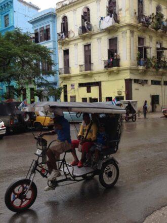 Havana pedi-cab and yellow building